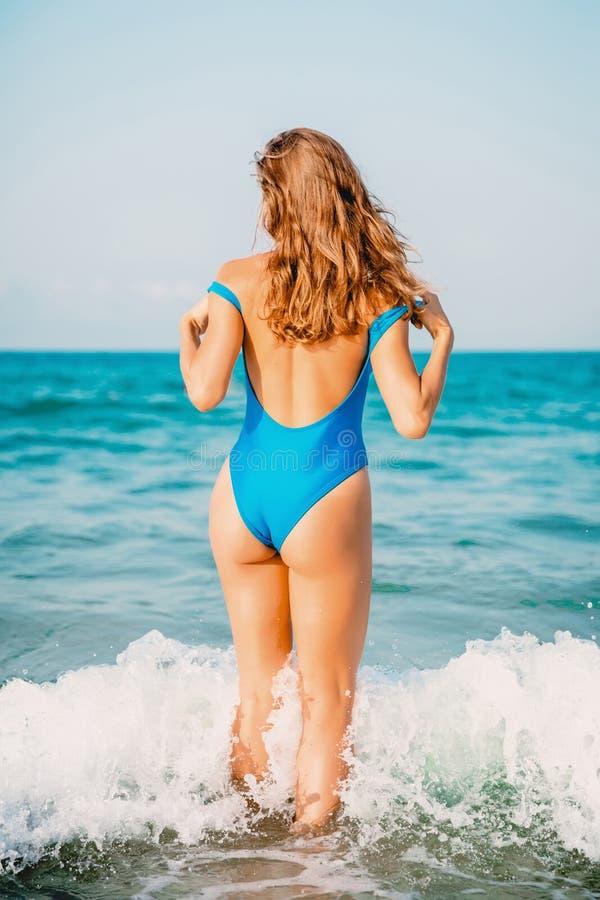 Ung attraktiv kvinna i blå swimwear på sandstranden Semester på havet royaltyfria foton