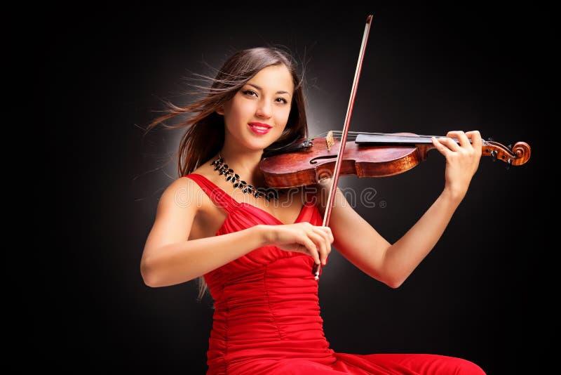Ung attraktiv kvinna i den röda klänningen som spelar fiolen arkivfoton