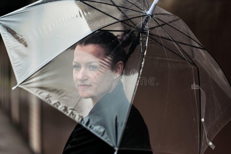 Ung attraktiv kvinna i svart posera för omslag som och för jeans är utomhus- mot bakgrund av byggnad arkivfoto