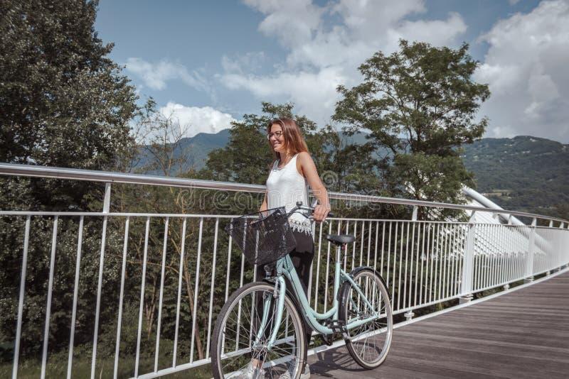 Ung attraktiv kvinna med cykeln p? en bro royaltyfri foto