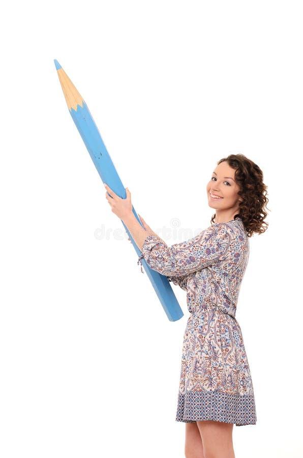 Ung attraktiv kvinna med den enorma blåttblyertspennan arkivfoto