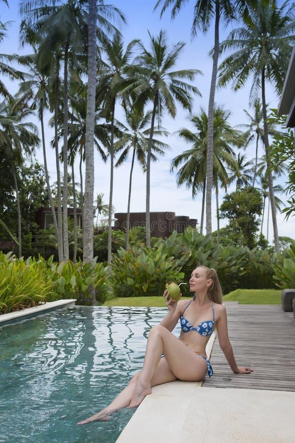 Ung attraktiv kvinna med långt hår i en swimwear i pölen med coctailen i kokosnöt fotografering för bildbyråer
