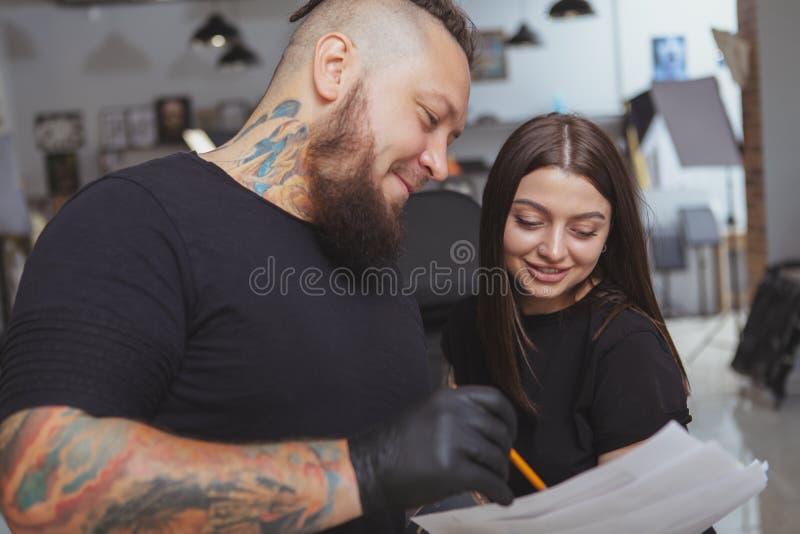 Ung attraktiv kvinna som får den nya tatueringen av den yrkesmässiga tattooisten arkivfoto