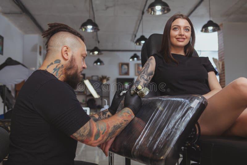 Ung attraktiv kvinna som får den nya tatueringen av den yrkesmässiga tattooisten fotografering för bildbyråer