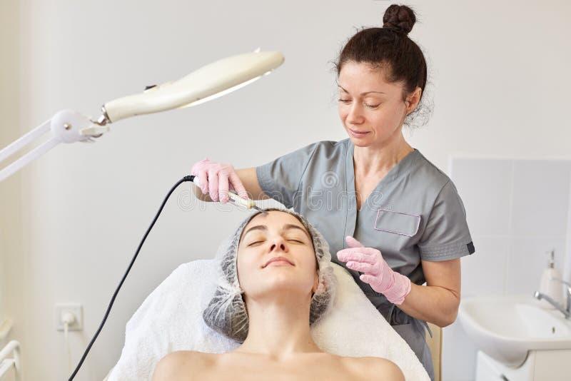 Ung attraktiv kvinna som får ultraljuds- ansikts- hud som rentvår behandling av den yrkesmässiga cosmetologisten, i skönhetsalong arkivbild