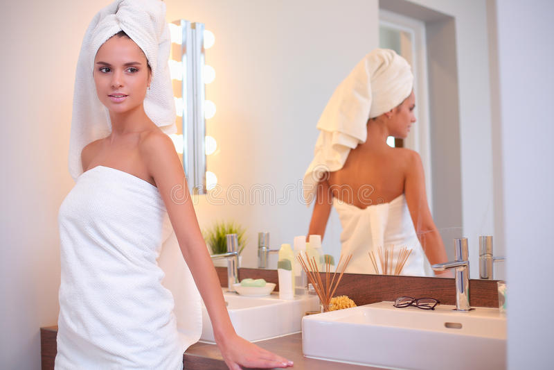 Ung attraktiv kvinna som framme står av badrumspegeln royaltyfri bild