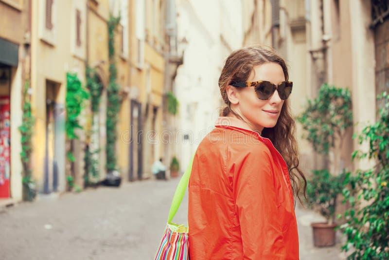Ung attraktiv kvinna som går i stad royaltyfri foto