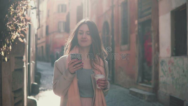 Ung attraktiv kvinna som går i stad och använder smartphonen Flicka som pratar med vänner och dricker kaffe arkivbild