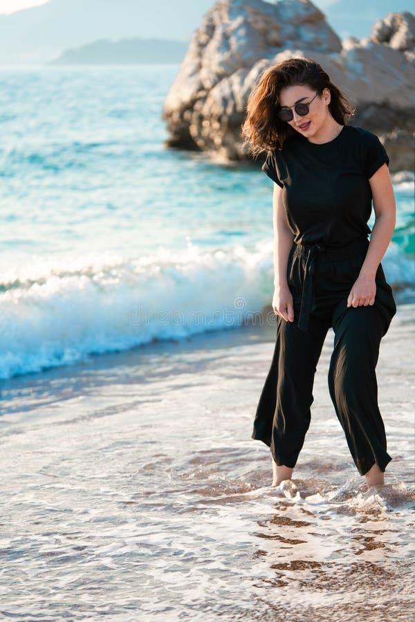 Ung attraktiv kvinna som g?r p? en solig strand p? kusten Handelsresande och blogger arkivbild