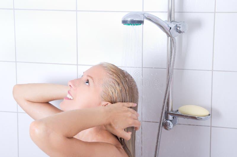 Ung attraktiv kvinna som har en dusch fotografering för bildbyråer