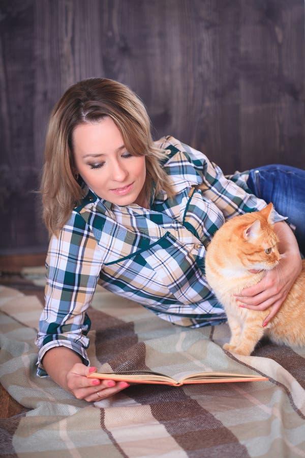 Ung attraktiv kvinna som läser en bok som ligger på golvet royaltyfria foton