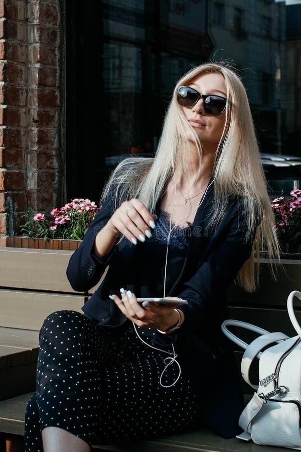 Ung attraktiv kvinna som lyssnar till musik på hennes smartphone, medan sitta på en gatabänk under ett lunchavbrott arkivfoton