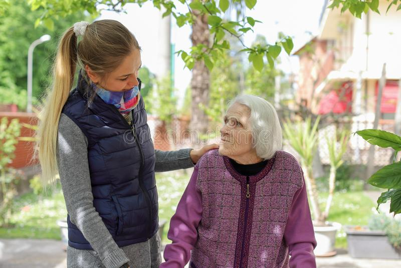 Ung attraktiv kvinna som omfamnar den utomhus- gamla farmodern Kvinnlig - utvecklingar - f?r?lskelse royaltyfri bild