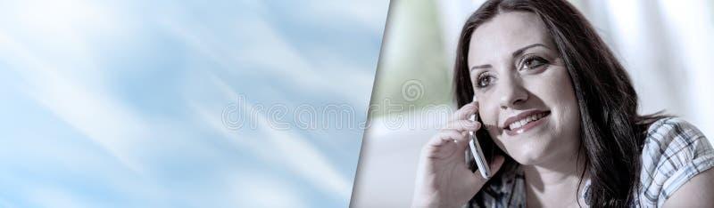 Ung attraktiv kvinna som talar på mobiltelefonen; panorama- baner arkivbild