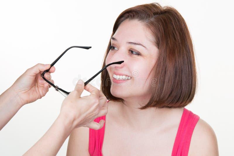 Ung attraktiv kvinna som testar nya exponeringsglas med optikerflickan royaltyfri fotografi