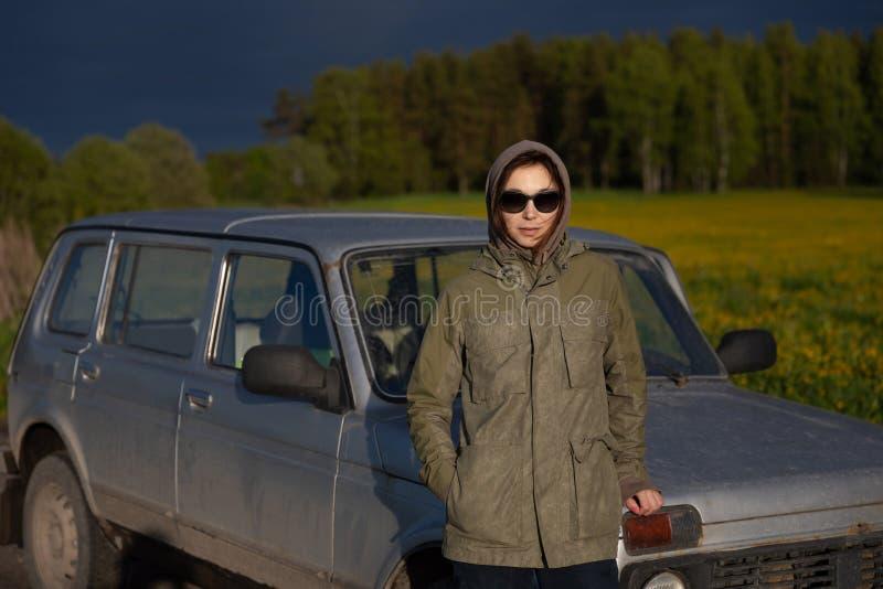 Ung attraktiv kvinna som utomhus poserar med hennes SUV p? en tom grusv?g mot bakgrunden av f?ltet royaltyfri fotografi