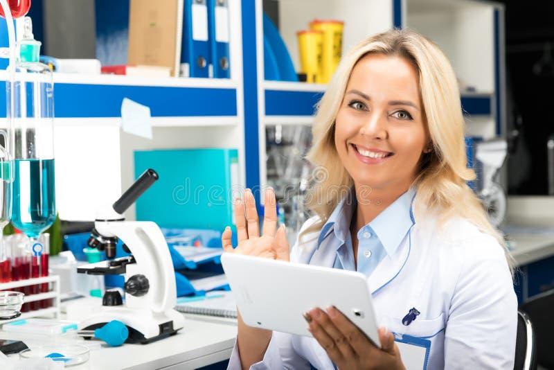 Ung attraktiv kvinnaforskare som använder minnestavladatoren i laen arkivbild