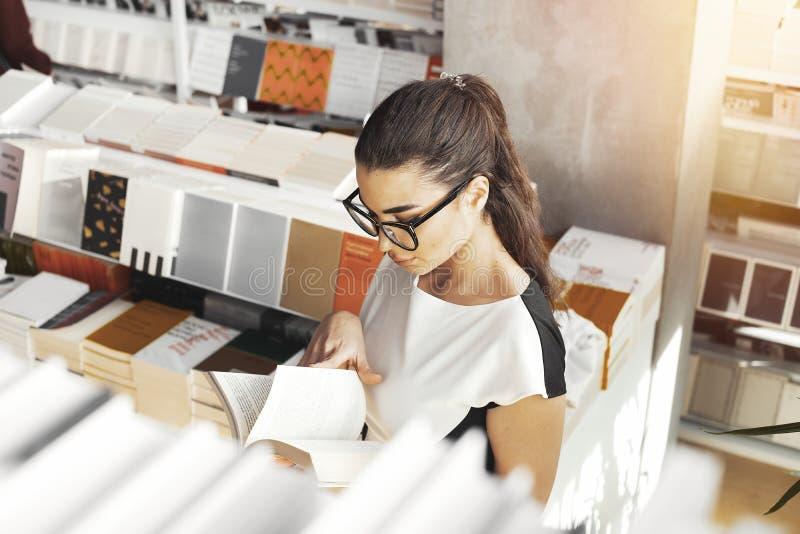 Ung attraktiv kvinnaläsebok i ett boklager, sikt från över arkivfoto