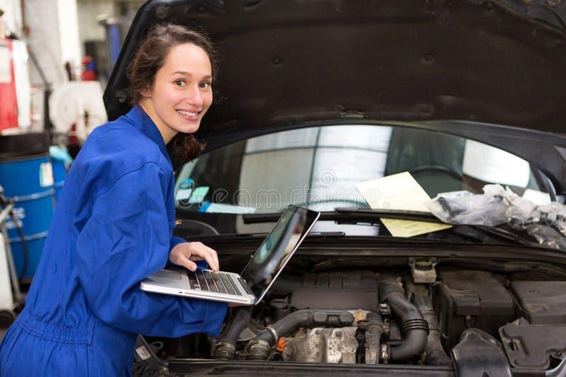 Ung attraktiv kvinnamekaniker som arbetar på garaget fotografering för bildbyråer