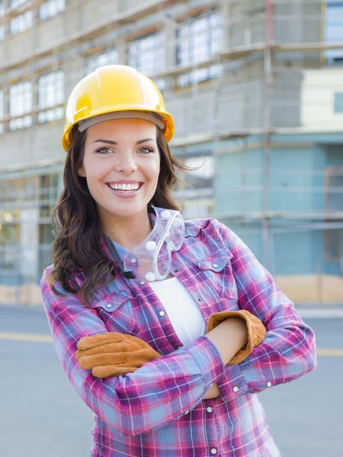 Ung attraktiv kvinnlig byggnadsarbetare Wearing Hard Hat och royaltyfri fotografi