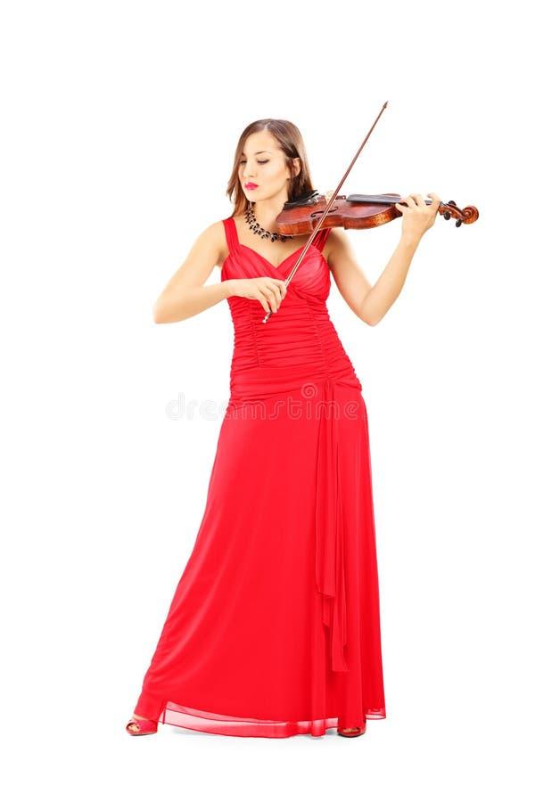 Ung attraktiv kvinnlig i den röda klänningen som spelar fiolen arkivbild