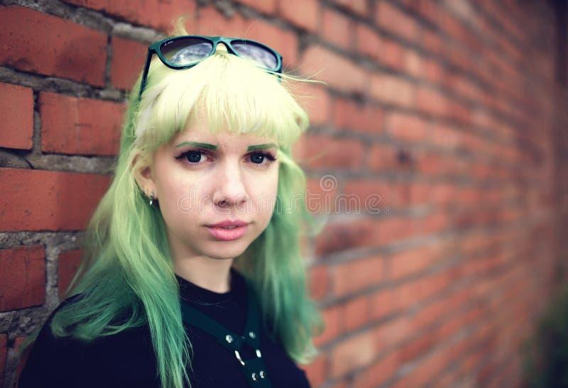 Ung attraktiv kvinnlig modemodell för stående med grönt håranseende vid tegelstenväggen royaltyfri foto