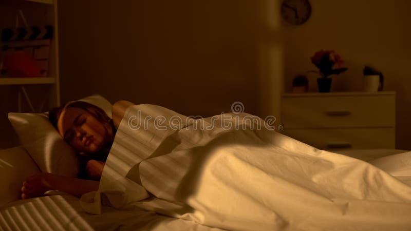 Ung attraktiv kvinnlig som sover fridfullt i säng, sunt vila, friskhet arkivfoto
