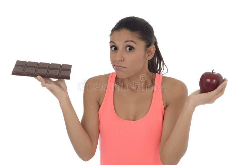 Ung attraktiv latinamerikansk kvinna i stång för frukt och för choklad för äpple för konditionöverkant hållande i henne händer fotografering för bildbyråer