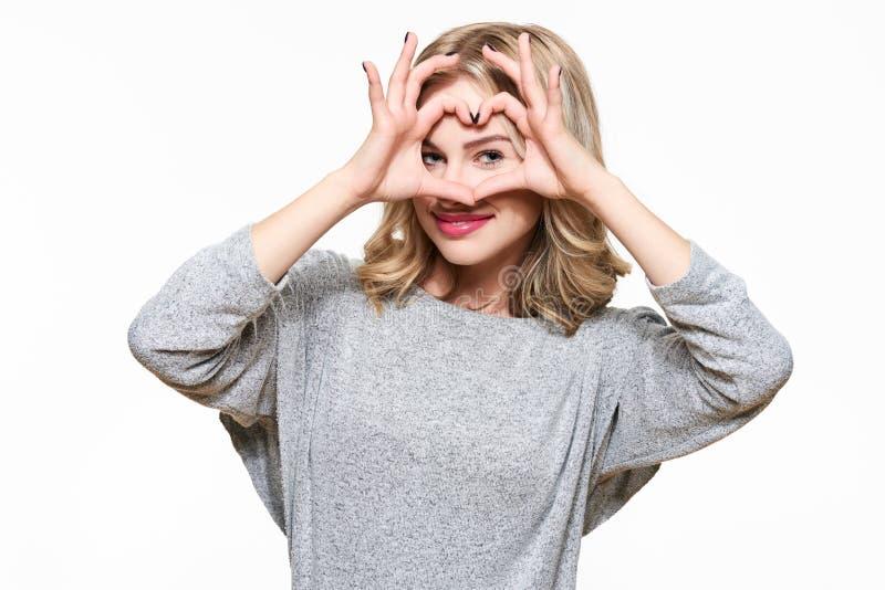 Ung attraktiv le gest för form för kvinnadanandehjärta med händer Closeup av att le symbol för flickavisningförälskelse fotografering för bildbyråer