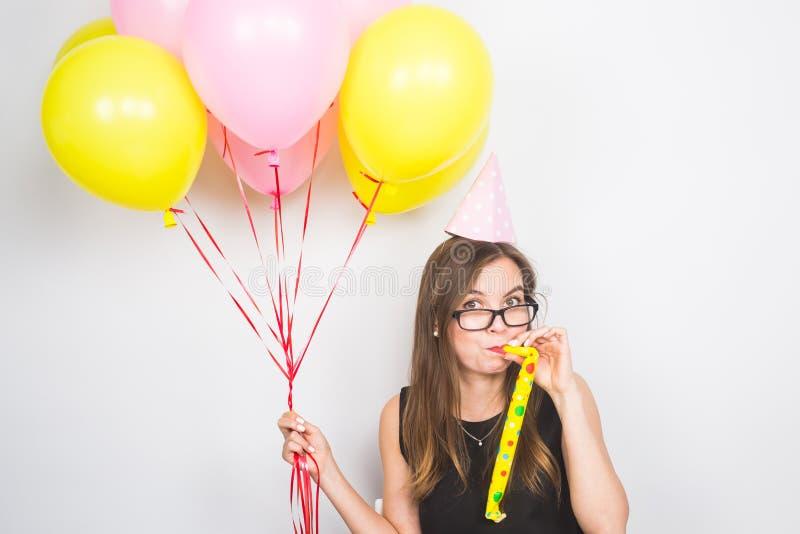 Ung attraktiv le kvinna med den födelsedaghatten, ballonger och visslingen på vit bakgrund Beröm och parti arkivbilder
