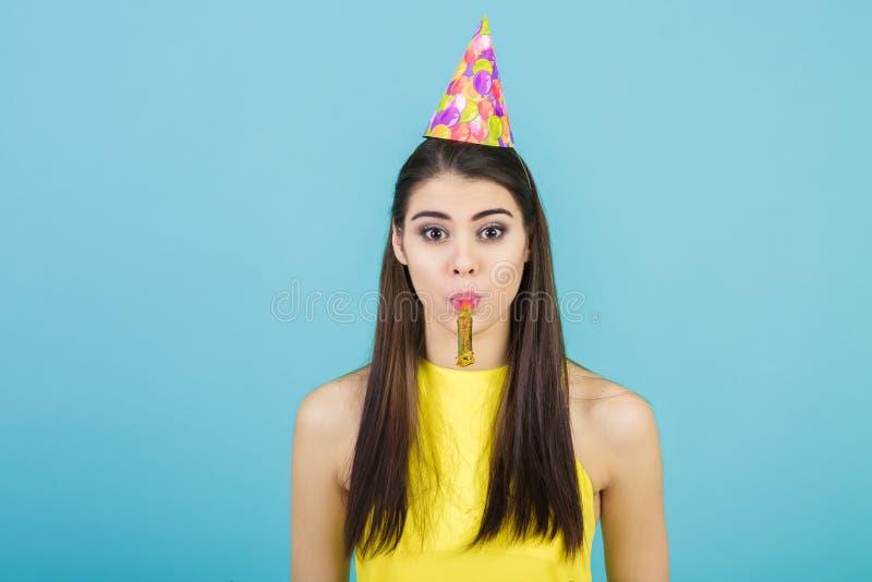 Ung attraktiv le kvinna med den födelsedaghatten och visslingen på blå bakgrund Beröm och parti royaltyfri fotografi