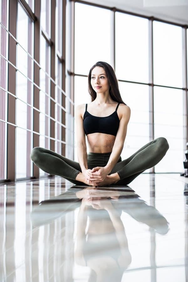 Ung attraktiv le praktiserande yoga för kvinnan som sitter i den halva Lotus övningen, Ardha Padmasana, poserar royaltyfri bild