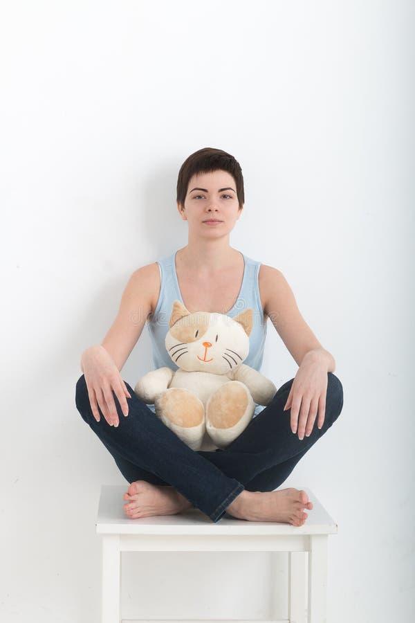 Ung attraktiv le praktiserande yoga för kvinnan som sitter i den halva Lotus övningen Ardha Padmasana, poserar och att utarbeta a arkivbild