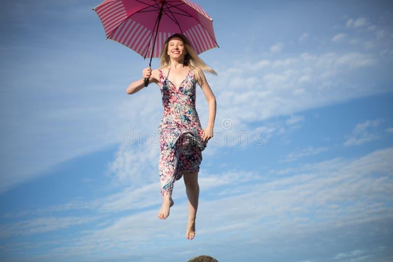 Ung attraktiv lycklig kvinnlig som hoppar i himmel med paraplyet royaltyfri foto