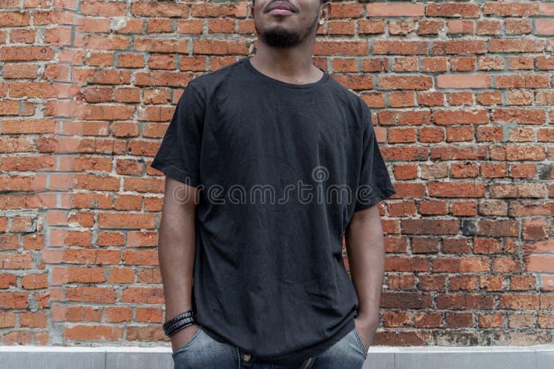 Ung attraktiv mörkhyad man i svart T-tröja på röd bricked bakgrund royaltyfri bild