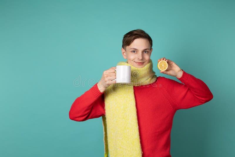 Ung attraktiv man i röd tröja och gula halsduken som gör den roliga framsidan och att rymma den vita koppen och den skivade citro arkivfoton