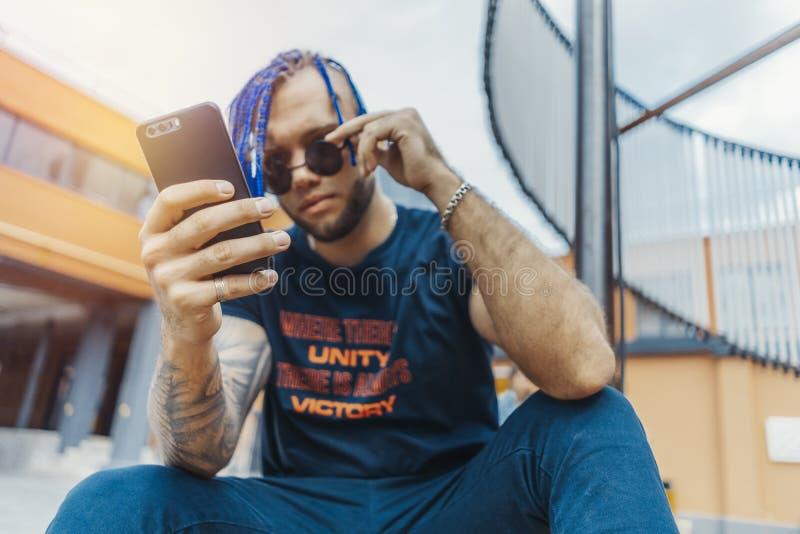 Ung attraktiv man med blåa dreadlocks som ser mobiltelefonskärmen royaltyfria foton