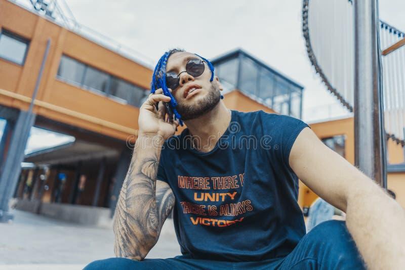 Ung attraktiv man med blåa dreadlocks som talar vid mobiltelefonen och trycker på hans hår royaltyfri foto