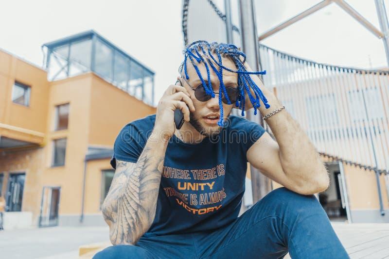 Ung attraktiv man med blåa dreadlocks som talar vid mobiltelefonen och trycker på hans hår arkivfoto