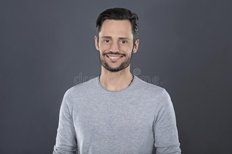 Ung attraktiv man med grått t-skjorta le som är lyckligt framme av en grå bakgrund fotografering för bildbyråer
