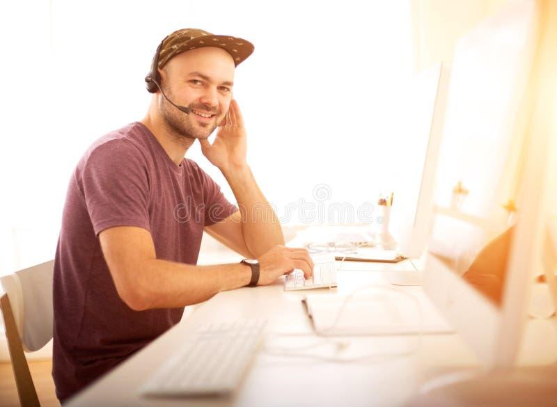 Ung attraktiv man som arbetar i en appellmitt royaltyfria bilder