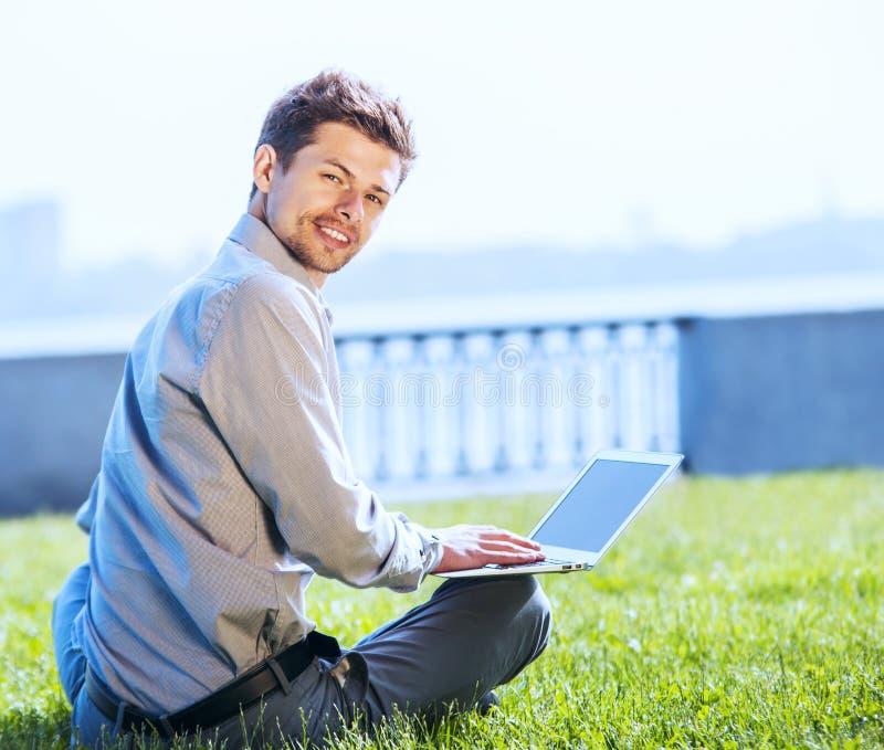 Ung attraktiv man som arbetar på den utomhus- bärbara datorn fotografering för bildbyråer