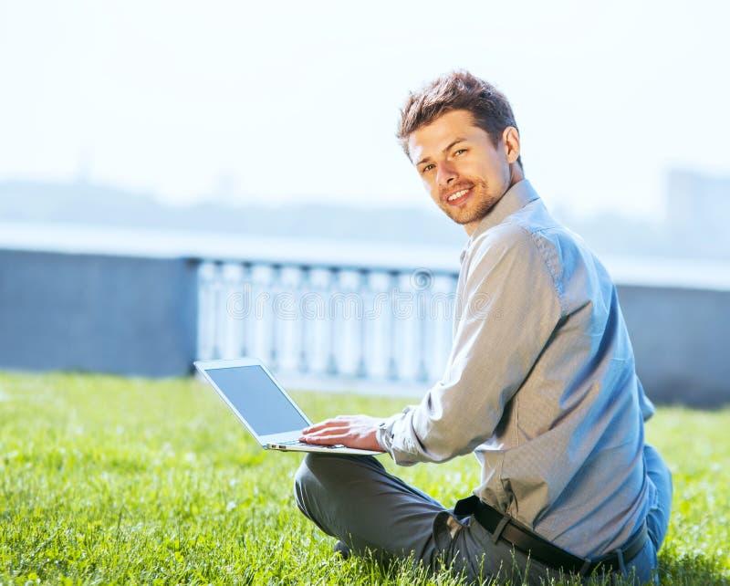 Ung attraktiv man som arbetar på den utomhus- bärbara datorn royaltyfria bilder