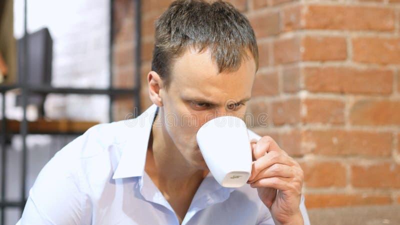 Ung attraktiv man som dricker ett kaffe i utrymme för idérikt arbete fotografering för bildbyråer