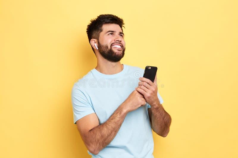 Ung attraktiv man som rymmer den smarta telefonen och listerning till radion royaltyfri bild