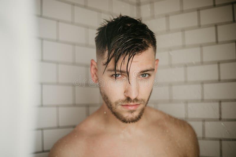 Ung attraktiv manlig modell Washing Hair i våt dusch för moderiktig modern gångtunneltegelplatta royaltyfri foto