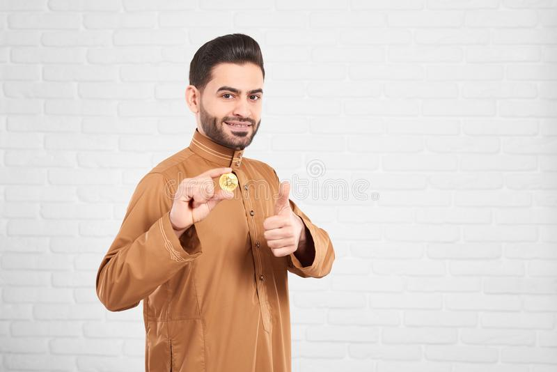 Ung attraktiv muslimsk manlig modell som är lycklig framlägga upp guld- bitcoin och tummar royaltyfri fotografi