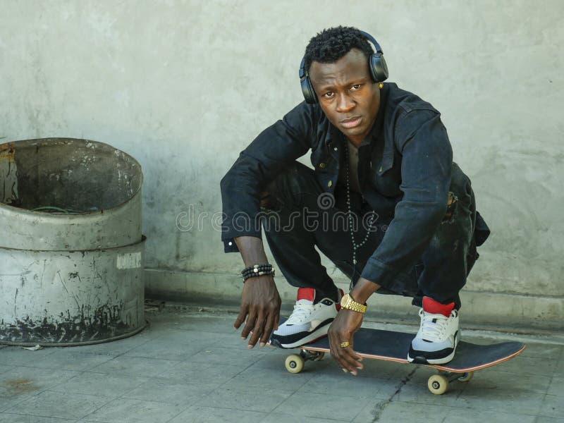 Ung attraktiv och allvarlig svart afro amerikansk man som squatting på skridskobräde på grungegatahörnet som ser kallt posera in royaltyfria foton
