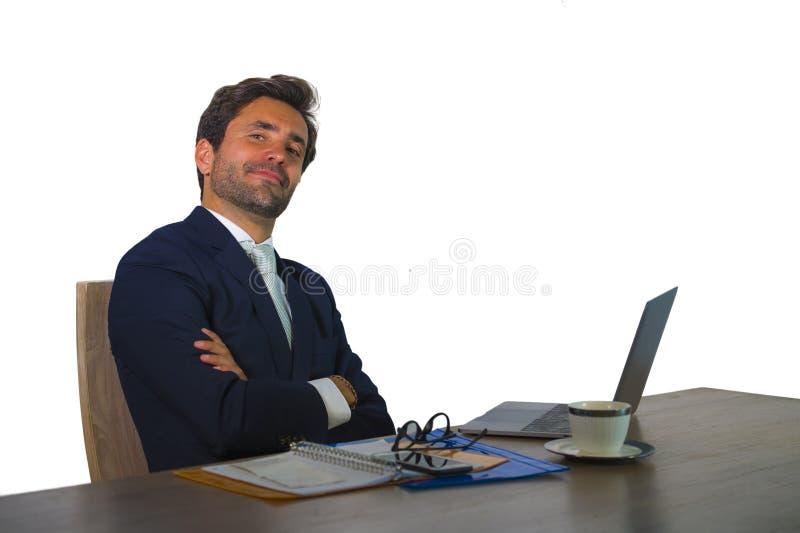 Ung attraktiv och effektiv affärsman som arbetar på skrivbordet för kontorsbärbar datordator som är säkert, i att le som är lyckl arkivbild