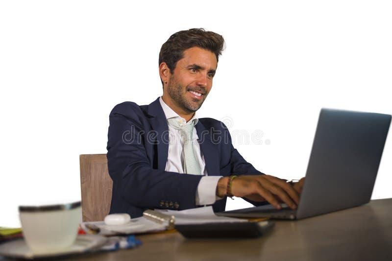 Ung attraktiv och effektiv affärsman som arbetar på skrivbordet för kontorsbärbar datordator som är säkert, i att le som är lyckl royaltyfria foton
